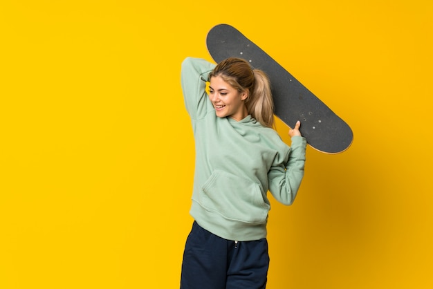 Blonde teenager skater girl  on yellow
