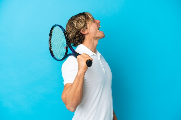 Blonde tennis player man isolated on blue background laughing in lateral position