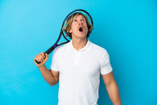 파란색 벽을 찾고 놀란 표정으로 고립 된 금발 테니스 선수 남자