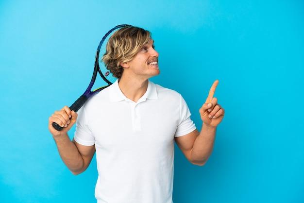 좋은 아이디어를 가리키는 파란색 벽에 고립 된 금발 테니스 선수 남자