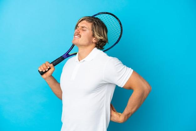 努力したために腰痛に苦しんでいる青い壁に孤立した金髪のテニス選手の男