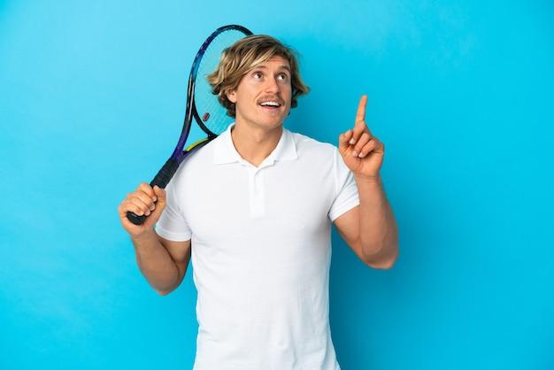 손가락을 가리키는 아이디어를 생각하는 파란색 벽에 고립 된 금발 테니스 선수 남자