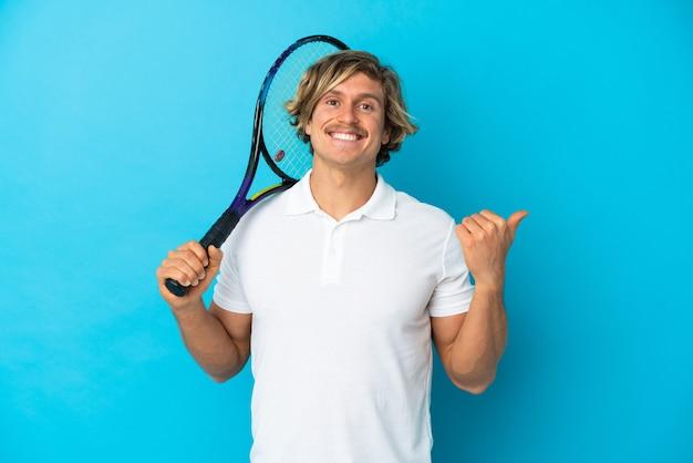 제품을 제시하기 위해 측면을 가리키는 절연 금발 테니스 선수 남자