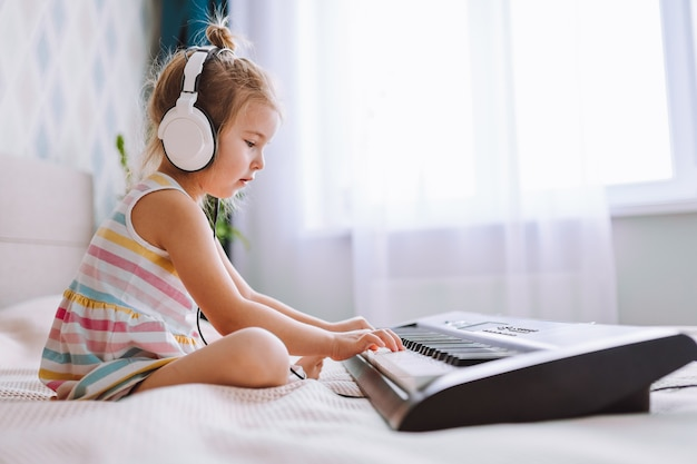 Blonde toddler girl wearing big earphones play classic digital piano at home sitting on bed. online education concept, quarantine.