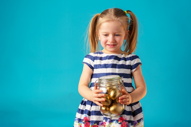 Blonde toddler girl with glass jar full of golden painted eggs for easter