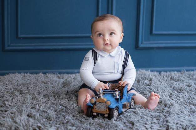 Белокурый малыш сидя на ковре и играя с голубым автомобилем.
