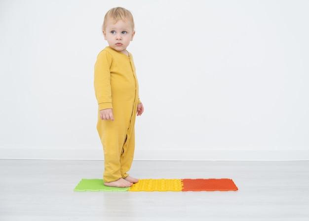 整形外科マットの上に立っている金髪の幼児