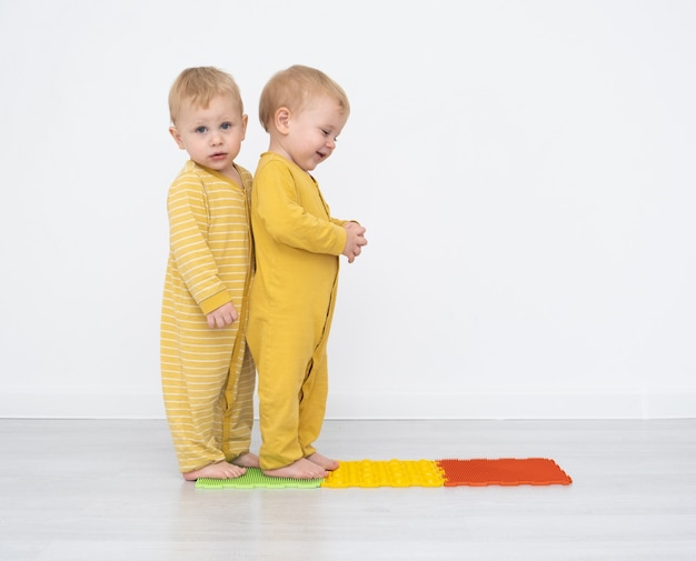 Blonde toddlers standing on an orthopedic mat