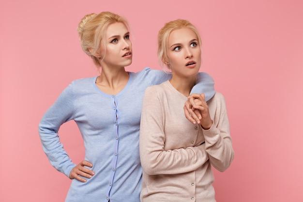 Белокурые сестры-близнецы удивленно смотрят вверх, одна из них явно недовольна увиденным. стоит на розовом фоне.