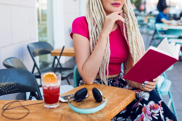Blonde unusual woman with dreadlocks sitting in cafe on the street, holding notebook, enjoying free time. wearing bright pants with tropical print.