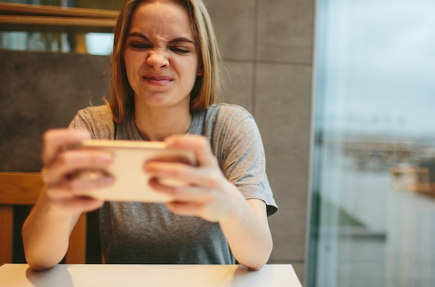 The blonde uses the phone. girl and smartphone. a woman is sitting in a cafe with a cellular