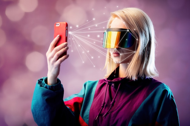 Blonde in vr glasses hold mobile phone with face scanning algorithm