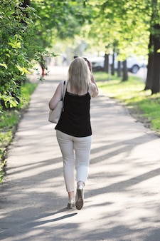 Blonde walks down a spring alley - back view