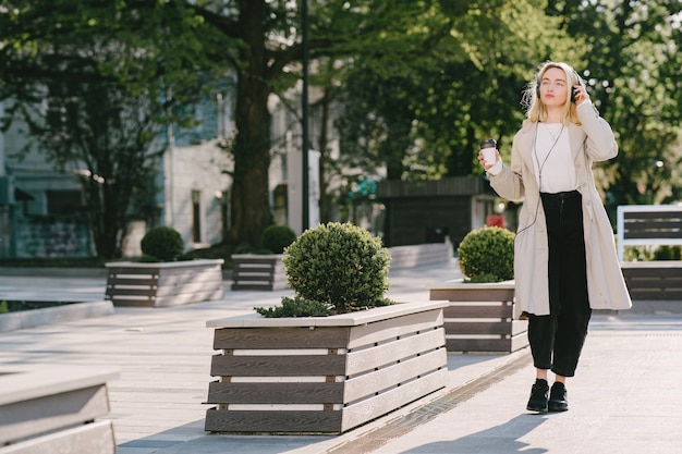 Blonde walks in summer city with cup of coffee