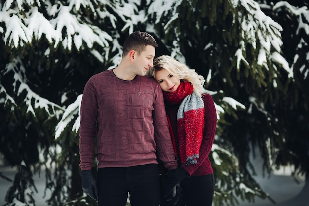 Blonde wife leaning on shoulder her husband at winter forest.