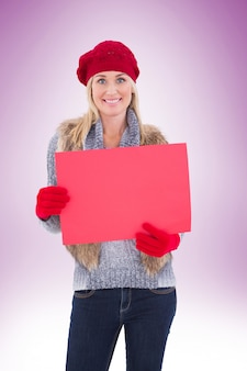 Blonde in winter clothes holding red sign