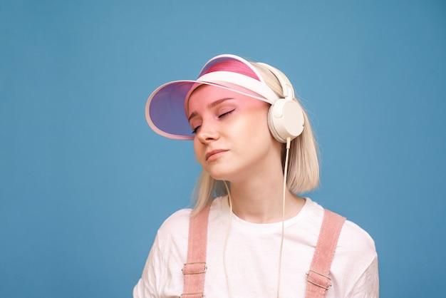 Блондинка в розовой кепке и белой футболке стоит на синей стене и слушает музыку в наушниках с закрытыми глазами