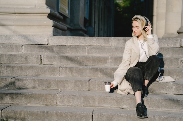 Blonde with headphones sitting on a stairs