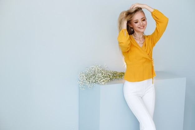 Blonde with healthy hair on a stylish background. free space for text