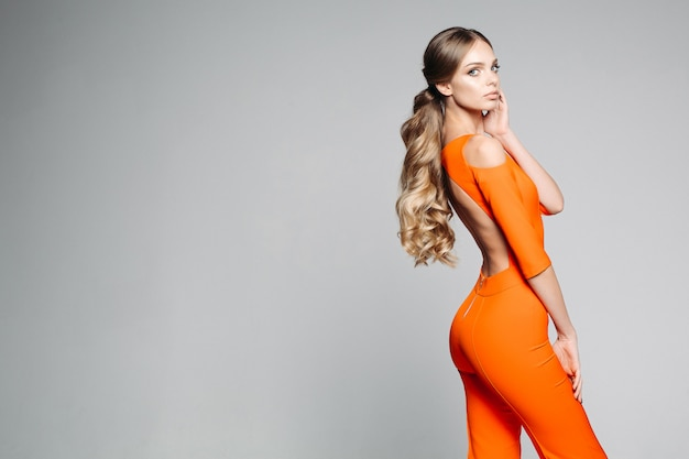 Blonde with long beautiful hair in an orange outdoor suit posing, not looking at the camera.