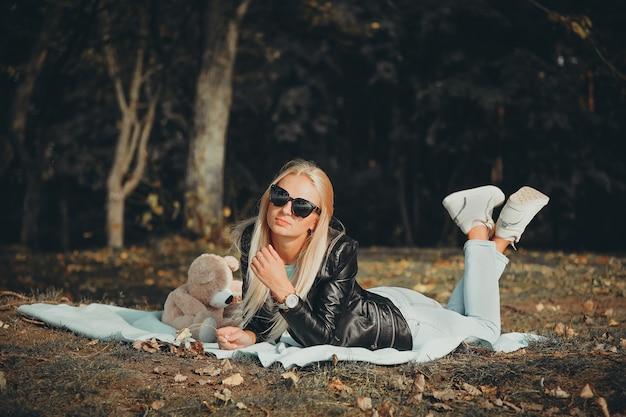 Блондинка с длинными волосами и в черной куртке лежала на одеяле на берегу