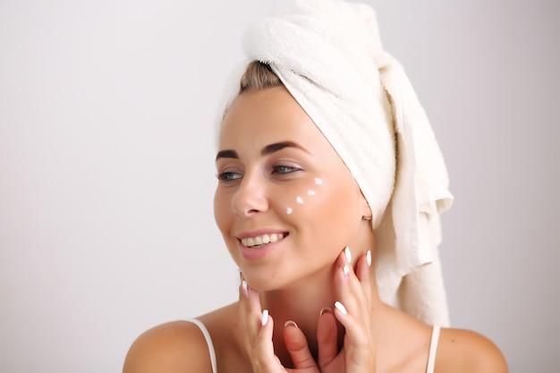 彼女の顔に触れる自然な皮膚を持つブロンド