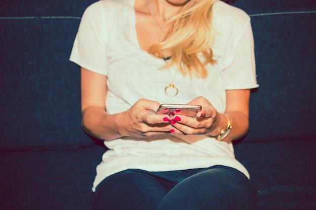 Bionda con il telefono sul divano