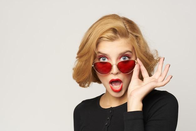 Блондинка с короткими волосами в солнцезащитных очках черной куртке обрезала вид на светлом фоне.