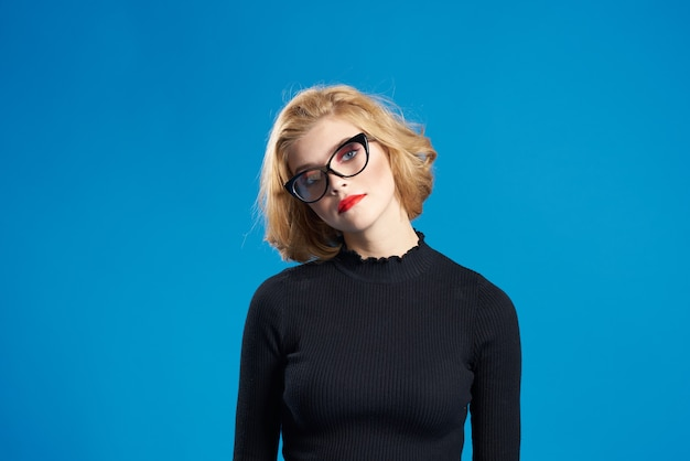 Blonde with short hair red lips glasses black jacket blue isolated background.