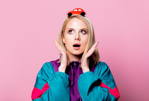 Blonde woman in 90s sport suit with toy car on pink wall