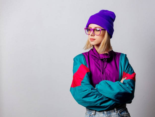 Blonde woman in 90s style jacket and hat with glasses