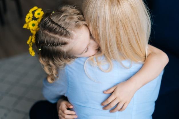 Блондинка и ее кудрявая маленькая дочь обнимаются дома в уютной гостиной