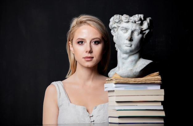Blonde woman next to an antique bust of a man on books