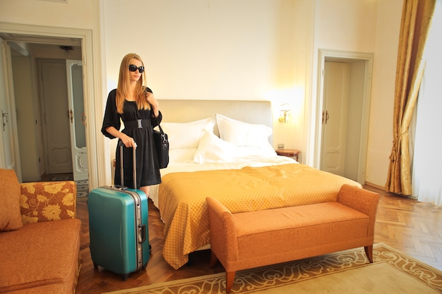 Blonde woman arriving to a hotel room
