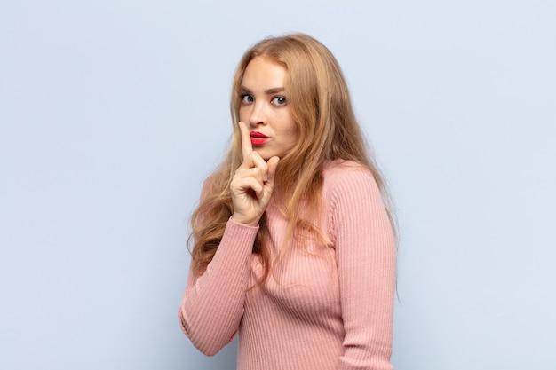 Блондинка просит тишины и тишины, жестикулирует пальцем перед ртом, говорит тсс или держит в секрете