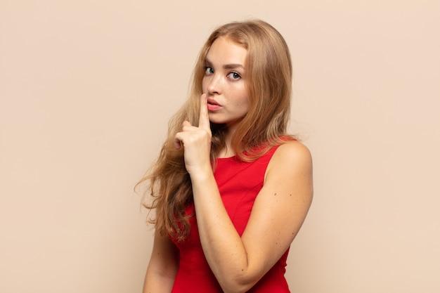 沈黙と静けさを求める金髪の女性、口の前で指で身振りで示す、shhと言うか秘密を守る