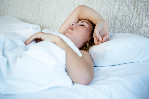 Blonde woman asleep in a white bed on her own