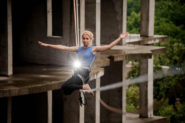 Белокурая женщина балансирует высоко на слэклайне