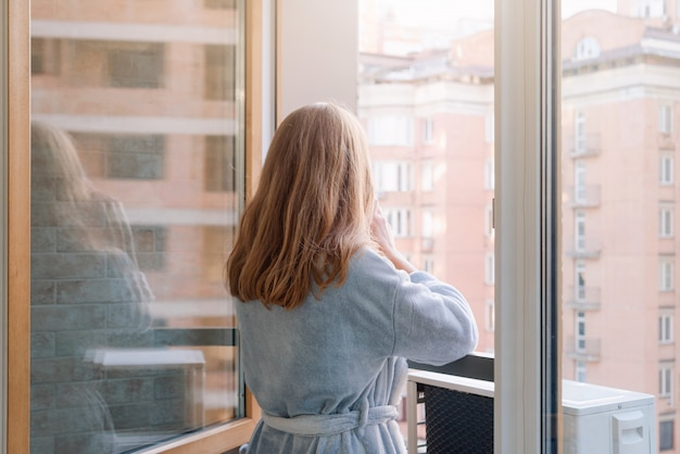 Blonde woman in bathrobe drinking her morning coffee or tea on a downtown balcony.