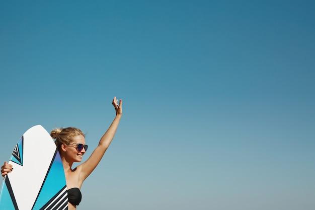 Donna bionda in spiaggia con il surf