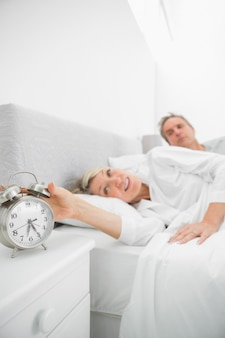Blonde woman in bed with partner turning off alarm clock at home in bedroom