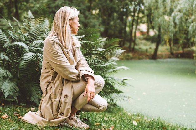 Blonde woman in a beige trench in a park.