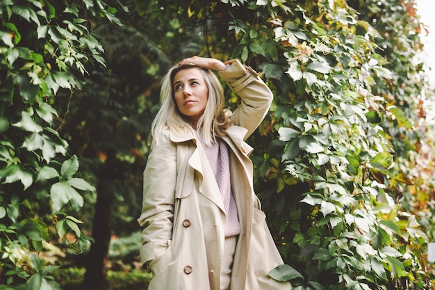 Blonde woman in a beige trench on a sunny day in the park.