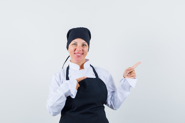 Blonde woman in black cook uniform pointing right with index fingers and looking pretty