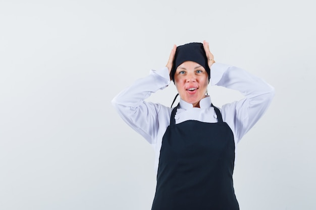 Blonde woman in black cook uniform putting hands on head and looking pretty