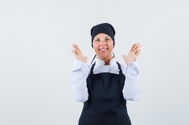 Blonde woman in black cook uniform stretching hands as inviting to come and looking pretty , front view.