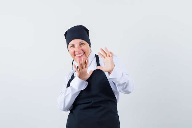 Blonde woman in black cook uniform stretching hands as stopping something and looking pretty , front view.