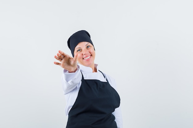 Blonde woman in black cook uniform stretching hands toward camera and looking pretty , front view.