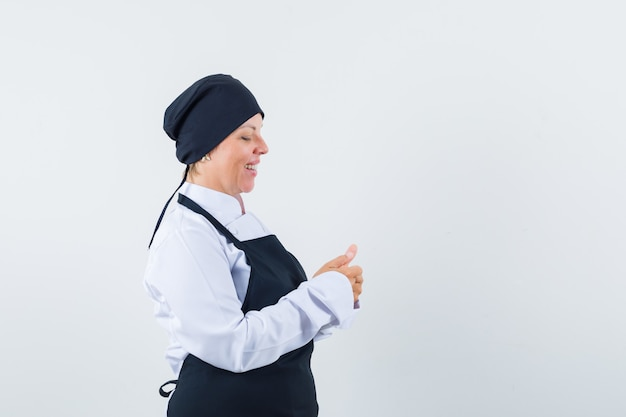 Blonde woman in black cook uniform stretching and rubbing hands and looking pretty