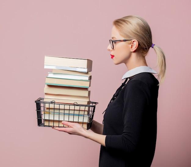 Блондинка в черном платье и очках держит корзину с книгами на розовой стене